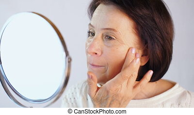 Woman moisturizes the face with cream - Middle aged woman...