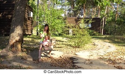 Woman mom with girl on wooden seesaw under tree - Young mom...