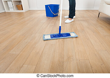 Woman Mopping Hardwood Floor At Home - Low section of young...