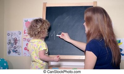 Woman mother and girl daughter writing word mother with...