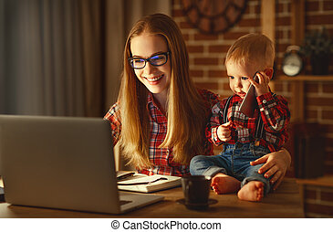woman mother working  with a baby at home behind a computer