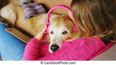 Woman mounting headphone on dogs ear on sofa 4k - Rear view...