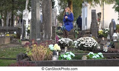 woman mourning near marble tombstone in cemetery in autumn. 4K
