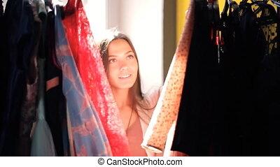Woman moves apart hangers on rack choosing dress inside room