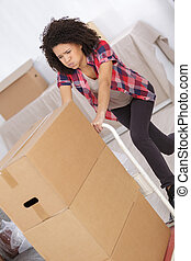 woman moving heavy card boxes