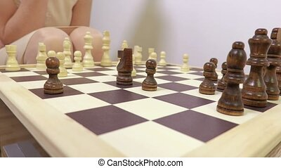 Woman moving pawn on chessboard close up
