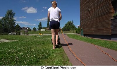 Woman mowing lawn in backyard of his house. Gimbal movement...