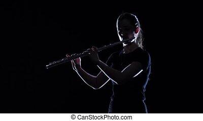 Woman musician blows motif in flute in slow motion. Studio