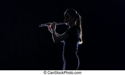 Woman musician blows the motif in wind instrument. Black studio