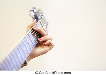Woman musician holding a guitar, playing a G chord - Woman...