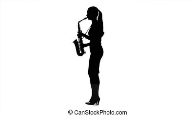 Woman musician playing on saxophone in slow motion. Black silhouette
