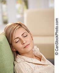 Woman napping in armchair at home