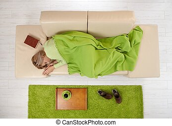 Woman napping on couch at home
