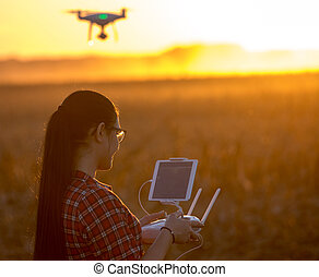 Woman navigating drone above farmland - Young farmer woman...