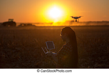 Woman navigating drone above farmland