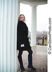 Woman near a column in the park