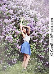 woman near a lilac bush, tinted