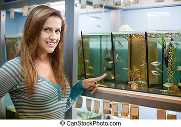 Woman near aquariums with fishes