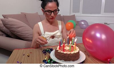 Woman near birthday party cake with burning candles