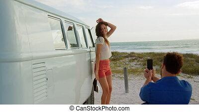 Woman near caper van on the beach 4k - Rear view of ...