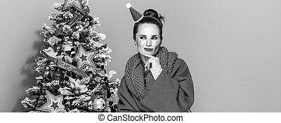 woman near Christmas tree isolated on yellow background -...