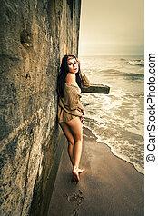 Woman near concrete constructions on the sea shore -...