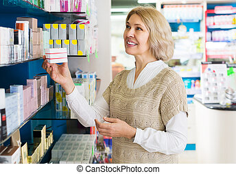 Woman near counter in pharmacy