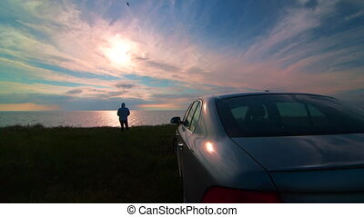Woman near his car on the sea coast at sunset