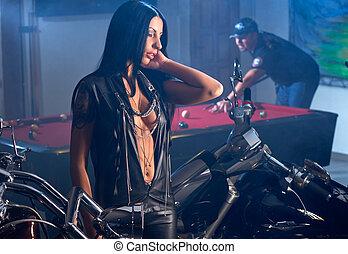 Woman near motorbikes, man playing billiards