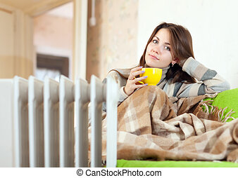 woman near oil heater at home - woman with yellow cup near...