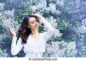 woman near the blue lilac, tinted