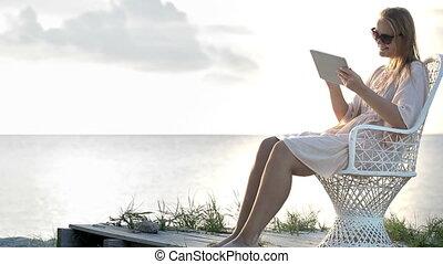 Woman near the sea watching photos using pad