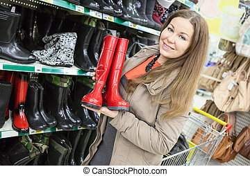 Woman near the shelves with watertights in store