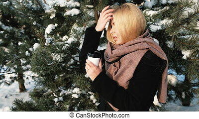 Woman near the tree with a closed cup waiting for someone.