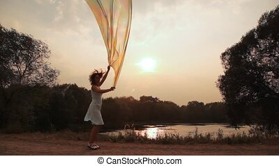 woman near to lake walks holds shawl fluttering on wind -...