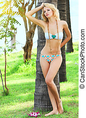 Woman near trunk of palmtree