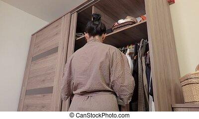 woman near wardrobe choosing her fashion outfit
