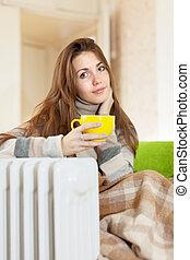 woman near warm radiator - smiling woman near warm radiator...