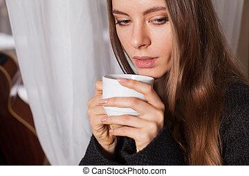 Woman near window drinking coffee