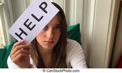 Woman need help. Sad woman holding help sign.