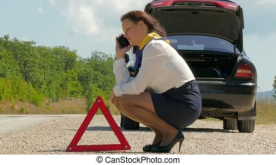 woman nervously talking on the phone next to a broken car