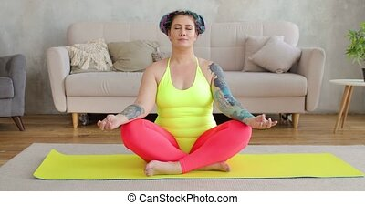 Fat woman newcomer in sport with braids in hairs are doing meditation sitting on yellow yoga mat in living room. Fitness exercises at home. Joke, mem, humor, parody. Workout, training concept.