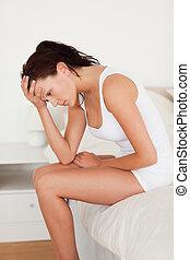 Woman not feeling well in her bedroom