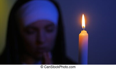 Woman nun praying at night. burning candles. Woman in clothes nuns. Blurry face, focus on fire of candle.
