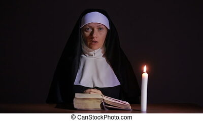 woman nun praying at night. burning candles. Woman in...