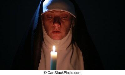 woman nun praying at night. burning candles. Woman in clothes nuns