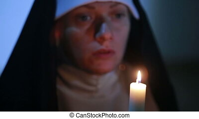 woman nun praying at night. burning candles. Woman in clothes nuns
