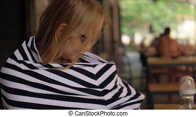 Woman nursing baby in cafe using milk snood