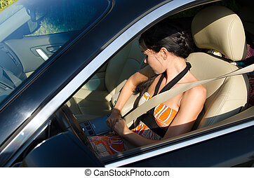 Woman driver obeying traffic rules and tightening her safety belt viewed through the open window of the car