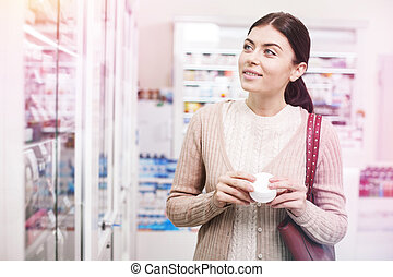 Woman observing shelves and holding a product in her hands